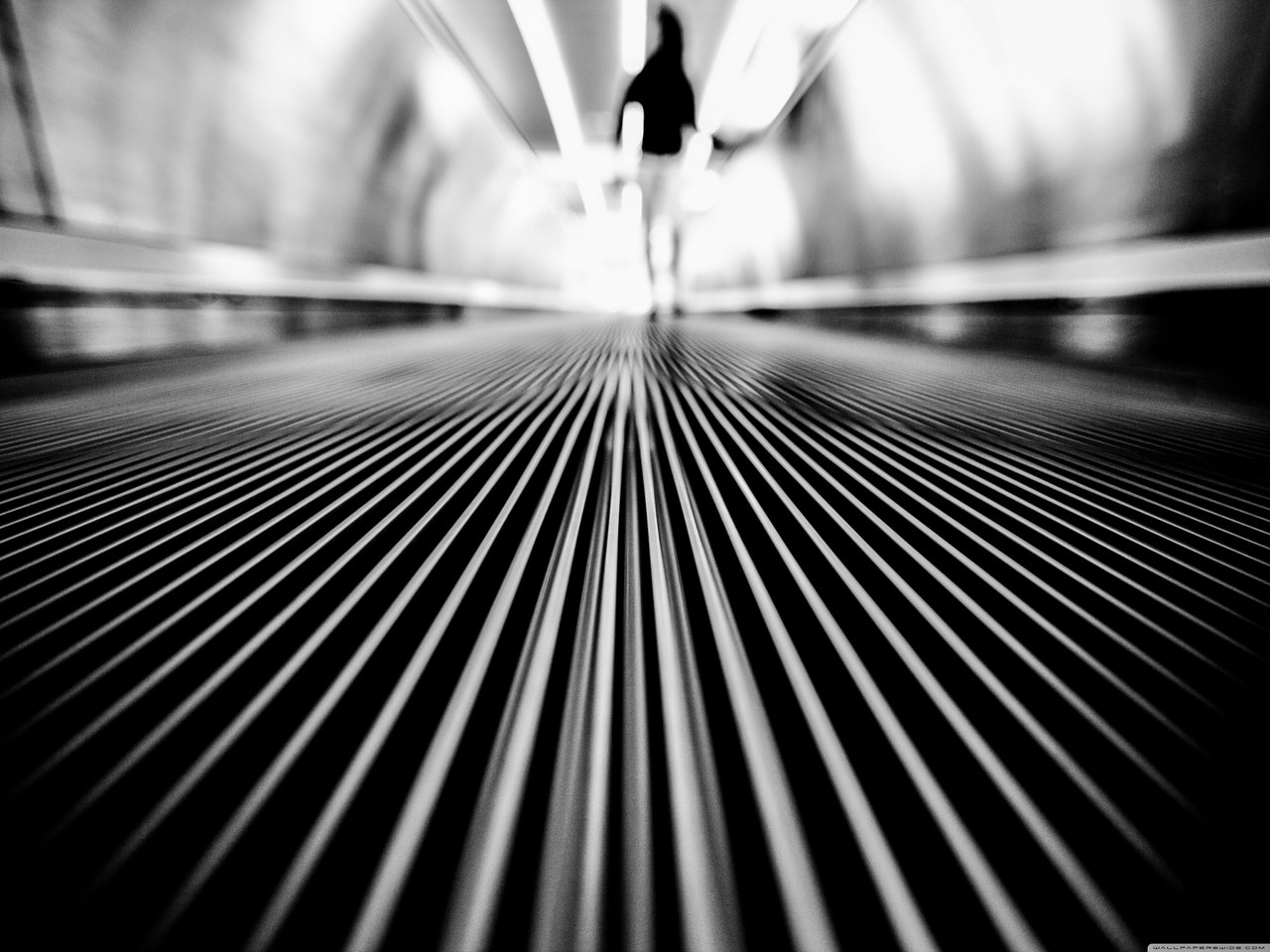 greyscale-photography-of-man-walking-on-tunnel-185661